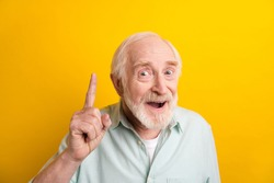 Photo of genius sweet age gentleman wear green shirt smiling pointing finger empty space isolated yellow color background