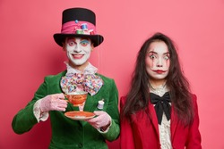 Photo of girl ghost has scarying makeup and pleased crazy hatter in costume drinks tea on party. Mysterious people on halloween fesitval. Spooky spouses couple come to masquerade pose indoor
