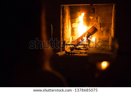 Photo of girl silhoette with glass near fireplace for graphic and web design, for website or mobile app #1378685075