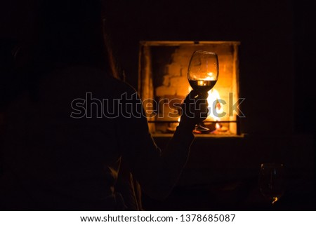 Photo of girl silhoette with glass near fireplace for graphic and web design, for website or mobile app #1378685087