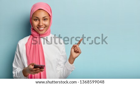 Photo of glad Arabic woman with gentle smile on face, points with fore finger on blank space, pink veil on head, holds mobile phone for texting messages, isolated against blue wall, browses internet #1368599048