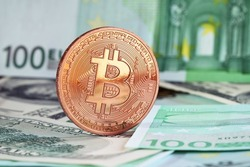 photo of golden bitcoins (new virtual currency) with traditional dollars and euro as a background .