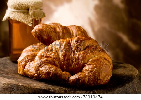 photo of golden fresh croissants with honey over on wooden table