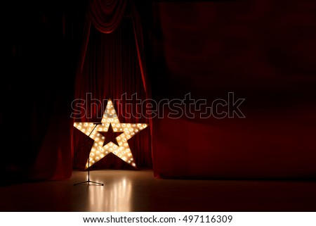 Photo of golden star with light bulbs on red velvet curtain on stage ストックフォト ©