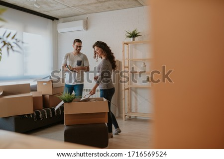Photo of good looking young couple having fun while unpacking boxes in new home on moving day. Young couple is moving in to their new home.