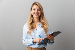 Photo of gorgeous blond secretary woman with long curly hair writing down notes in clipboard while working in office isolated over gray background