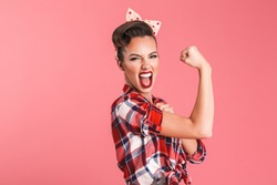 Photo of gorgeous strong young pin-up woman isolated over pink background wall showing biceps screaming.