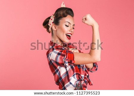 Photo of gorgeous strong young pin-up woman isolated over pink background wall showing biceps.