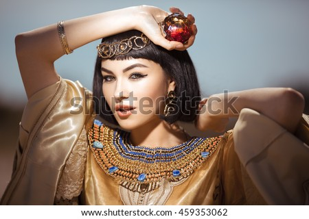 Stock Photo Photo of gorgeous woman with Cleopatra makeup, closeup portrait of beautiful female with stylish haircut agaist, young lady wearing fashionable golden necklace and holding magik ball outdoor, beauty