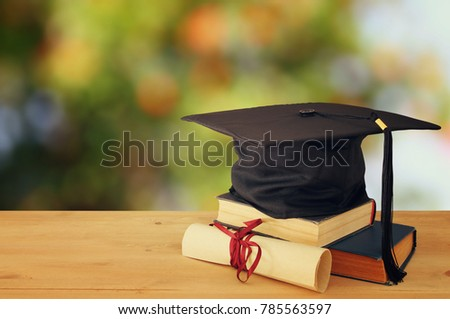photo of graduation black hat over old books next to scroll diploma on wooden desk. Education and back to school concept
