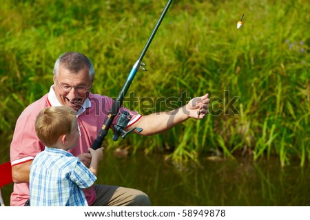 Photo of grandfather and grandson fishing in summer