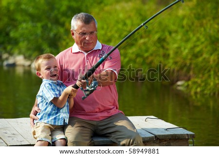 Photo of grandfather and grandson pulling rod while fishing on weekend