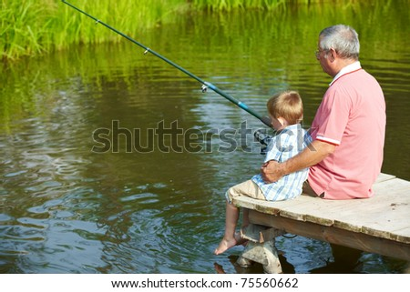 Photo of grandfather and grandson sitting on pontoon and fishing on weekend