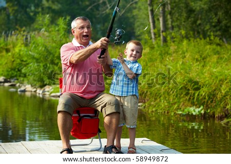 Photo of grandfather and grandson throwing fishing tackle in natural environment - stock photo