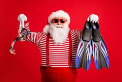 Photo of grandfather grey beard hold blue diving gear mask flippers smile, wear santa claus x-mas costume suspenders sunglass striped shirt cap isolated red color background