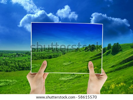 photo of green field in hands on nature background