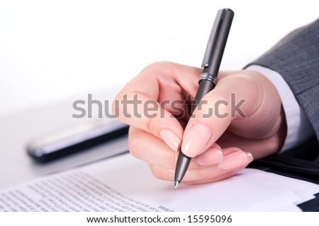 Photo of grey pen in hand over document at workplace