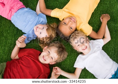 Photo of group of children lying on the grass together