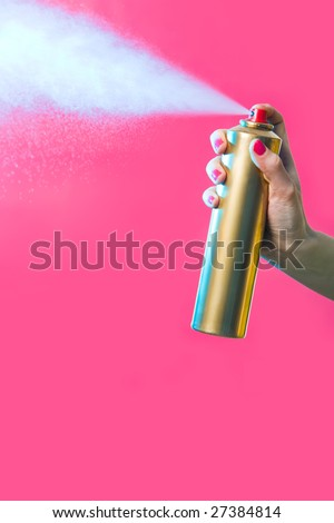 Photo of hair lacquer in female?s hand spraying it over red background