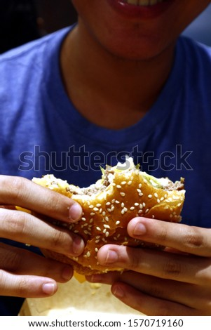 Photo of half eaten cheese burger with bites held by a person