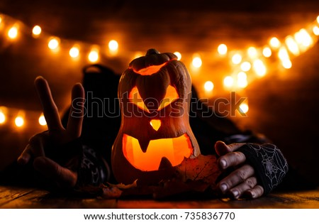Photo of halloween background with pumpkin and witch hands on wooden table against grunge bokeh lights background