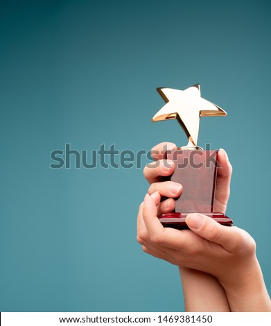 Photo of hand of human raising goblet with star #1469381450