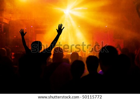 photo of hands at rock concert, silhouettes against stage lighting - stock photo
