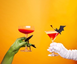 Photo of hands of mummy and zombies with wine glass and black bat on empty orange background .