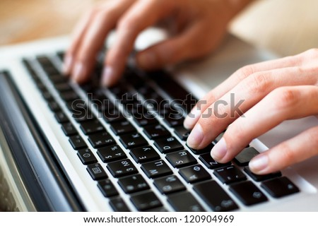 Photo of hands typing text on a laptop keyboard