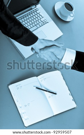 Photo of handshake of business partners after striking deal. Closeup.
