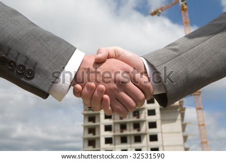 Photo of handshake of business partners after striking deal on background of building under construction - stock photo