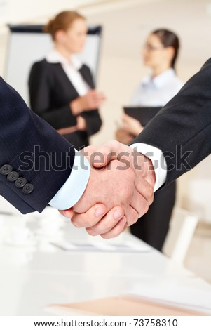 Photo of handshake of business partners after striking deal on background of communicating women