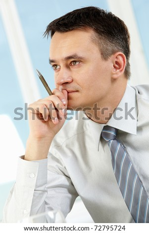 Photo of handsome businessman with pen in hand under inspiration