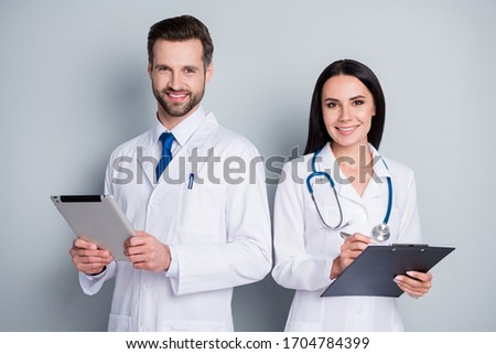 Photo of handsome busy family doc guy lady virology clinic listen client experienced doctors write paper online prescription tablet clipboard wear lab coats isolated grey color background