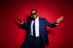 Photo of handsome dark skin business boss guy chilling resting corporate party event raise hands dancing star wear sun specs formalwear suit tuxedo isolated red burgundy background