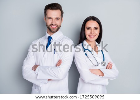 Photo of handsome doc guy lady patient consultation virology clinic stand back-to-back toothy smiling arms crossed experienced doctors wear lab coats isolated grey color background