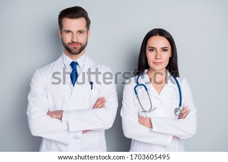 Photo of handsome doc guy professional lady patients consultation virology clinic listen client complaining arms crossed confident doctors wear lab coats isolated grey color background