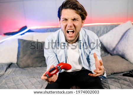 Photo of handsome excited guy sitting at comfy sofa, quarantine stay home gamer holding play station joystick, good mood fifa championship, Unhappy gamer player dissatisfied with video game.