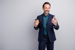 Photo of handsome friendly business man chief hold telephone hands read corporate email drink hot coffee to go formalwear blazer shirt trousers blue suit isolated grey color background