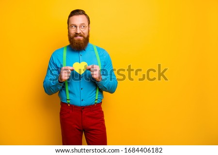 Photo of handsome funny guy hold little paper heart postcard showing feelings look curious empty space wear blue shirt green suspenders red pants isolated yellow color background