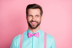 Photo of handsome guy trend clothes look side empty space know evil secret toothy smile cunning chatterbox person wear shirt suspenders bow tie isolated pastel pink color background