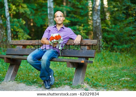 Photo of handsome guy with bouquet waiting for his girlfriend outside