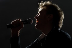 photo of handsome guy with microphone in hands