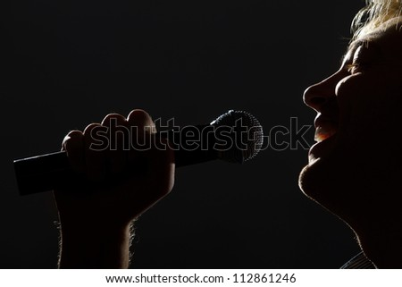 photo of handsome guy with microphone in hands - stock photo