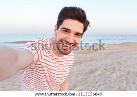 Photo of handsome happy young caucasian man make selfie by camera on the beach.