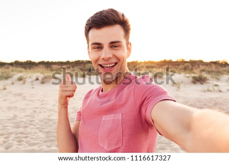Photo of handsome happy young caucasian man make selfie by camera on the beach showing thumbs up. #1116617327
