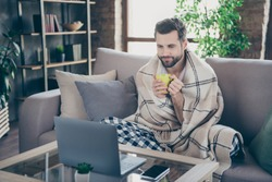 Photo of handsome homey guy sit comfy sofa saturday weekend drink fresh coffee watch film notebook stay home quarantine pajama covered checkered blanket living room indoors