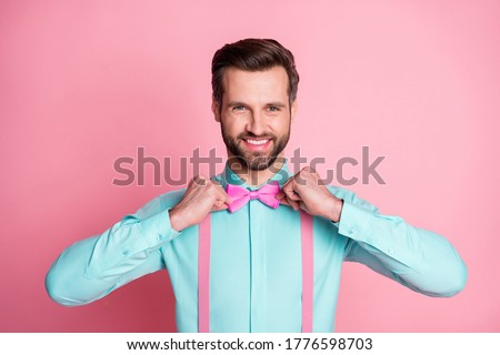 Photo of handsome macho guy trend clothes preparing corporate party retro theme well-dressed wear teal shirt suspenders bow tie isolated pastel pink color background Foto d'archivio ©