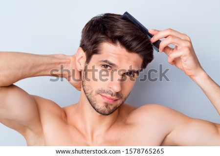 Photo of handsome macho man guy holding hand looking attentive mirror using hairbrush styling hairdo topless torso metrosexual hot tender body isolated grey background