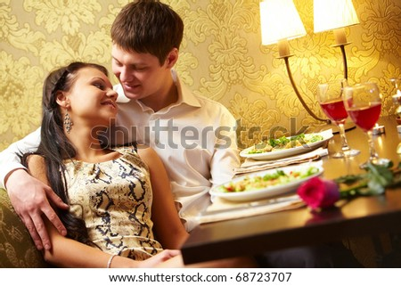 Photo of handsome man embracing with love his girl in the restaurant